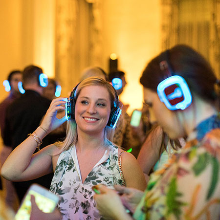 Girl listens to headphones at a party