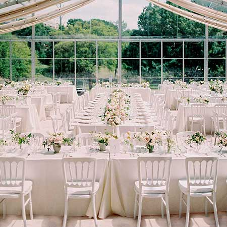 Tent decorated with white chairs and tables