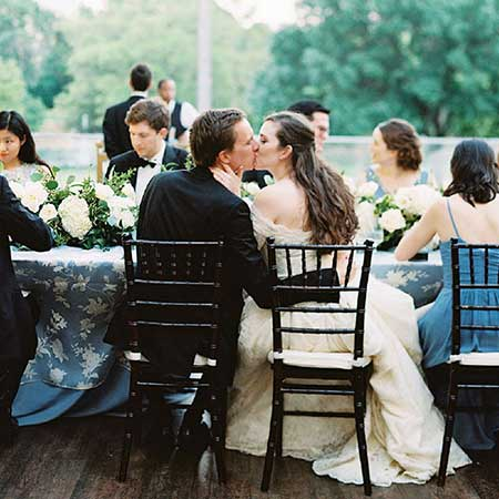 Bridal couple kiss at a table with guests